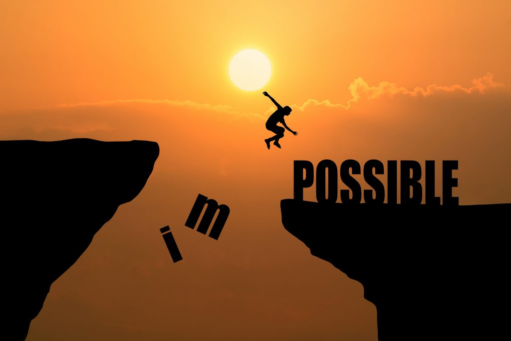 Conscious awakeness: Man jumping over cliff with the words impossible and possible at sunset